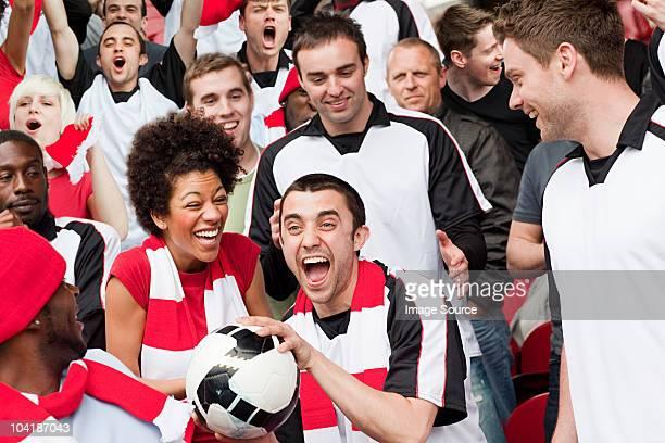 Homme dans une foule attraper un ballon de match de football