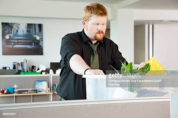 """man in cubicle packing stuff into a container - """"compassionate eye"""" stock pictures, royalty-free photos & images"""
