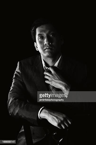 man in dark black and white in suit and tie