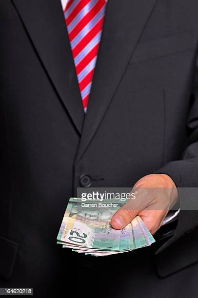 CONTENT] Man in dark suit holding Canadian currency