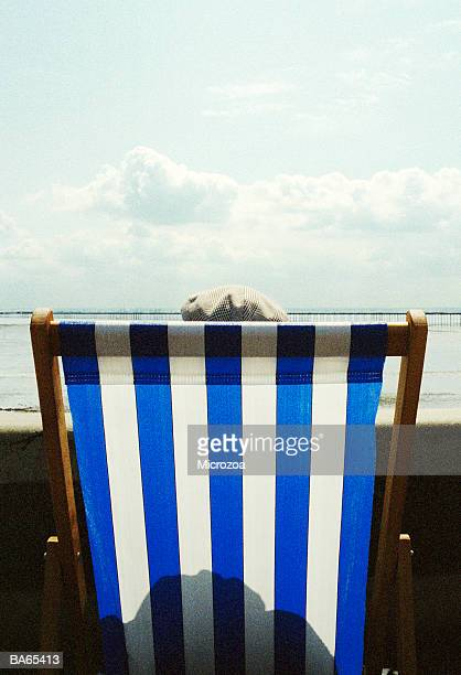 man in deckchair wearing flat cap, on promenade, rear view - microzoa fotografías e imágenes de stock