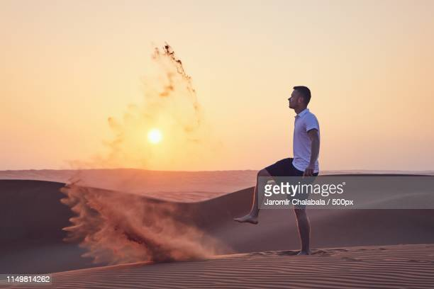 man in desert - kicking stock pictures, royalty-free photos & images