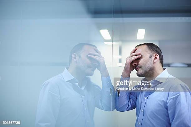 Man in despair facing reflective wall