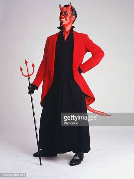 man in devil costume standing, smiling - devil costume stockfoto's en -beelden