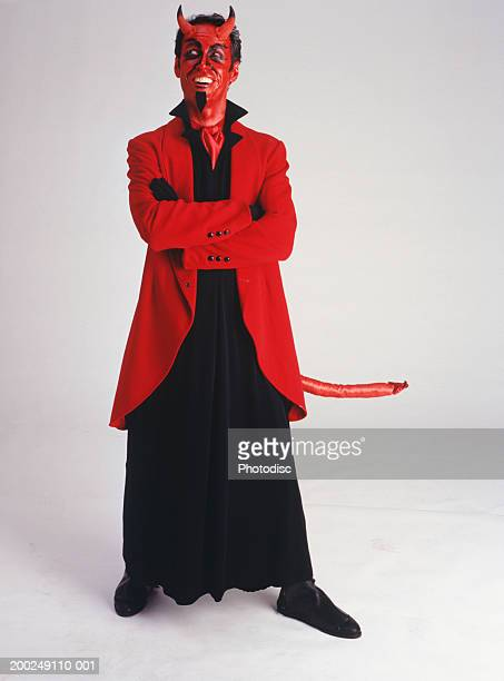 man in devil costume standing, smiling, (portrait) - devil costume stockfoto's en -beelden
