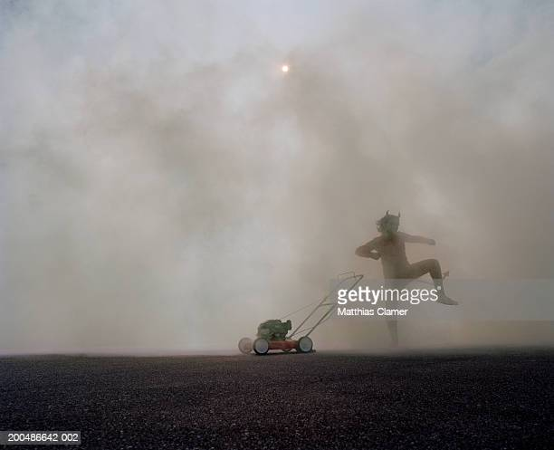 man in devil's costume dancing next to lawn mower in smoke - devil costume stockfoto's en -beelden