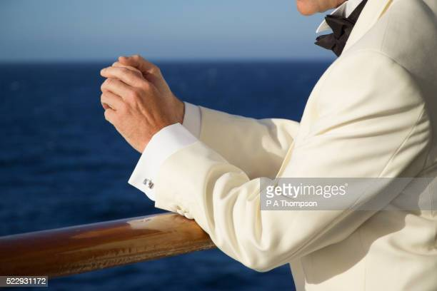 man in dinner jacket at ship's railing - white tuxedo stock pictures, royalty-free photos & images