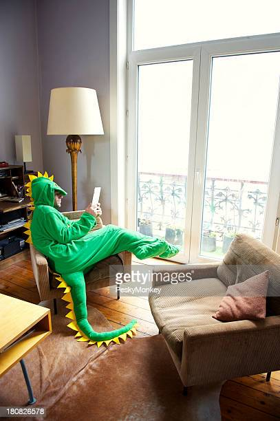 Man in Dinosaur Suit Relaxes Home Using Digital Tablet Computer