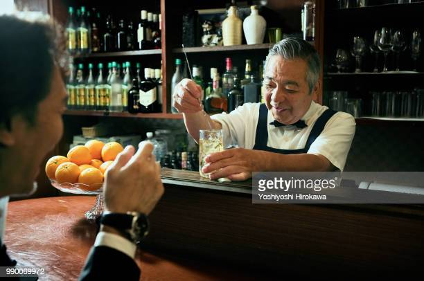 Man in discussion with bartender while seated at bar counter
