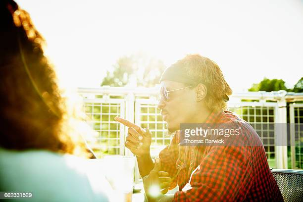 Man in discussion with friends on restaurant deck