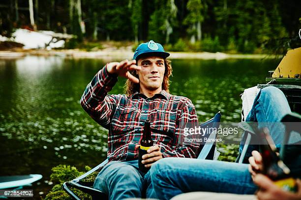 man in discussion with friends while camping - men friends beer outside stock pictures, royalty-free photos & images