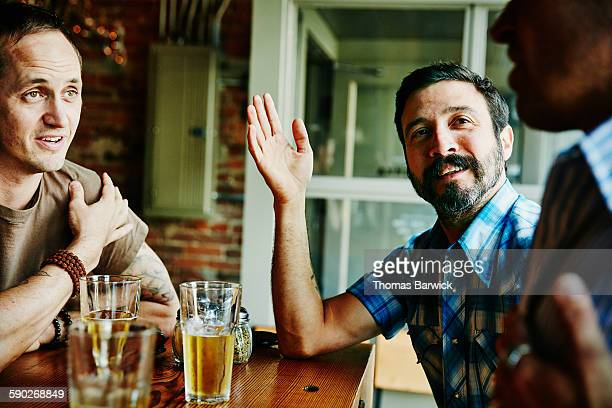 Man in discussion with friends while having drinks