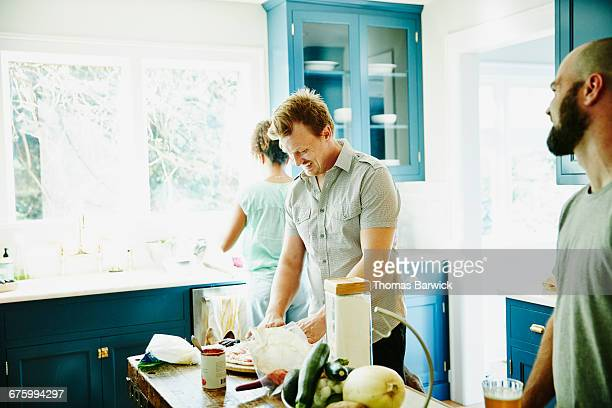 Man in discussion with friends while making pizza