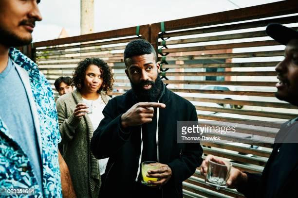 man in discussion with friends while sharing drinks at outdoor bar - wijzen handgebaar stockfoto's en -beelden