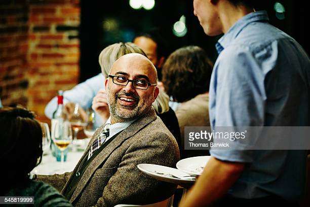 Man in discussion with server during dinner