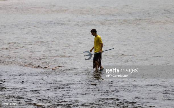 "Man in disguise carrying a trident walks in the river before the start of the 81th edition of the ""Descenso Internacional del Rio Sella 2017"" a 20km..."