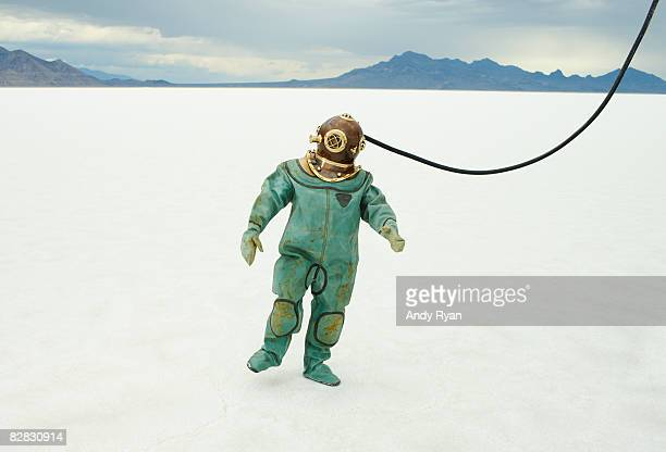 man in diving suit on salt flats. - scaphandrier casque photos et images de collection