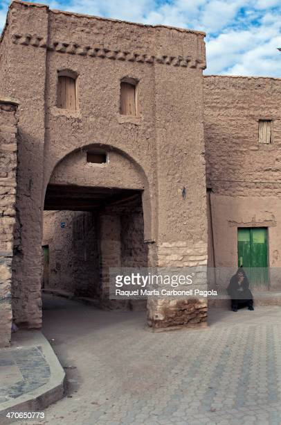 Man in djellaba sitting at a traditional adobe house doorway in a Ksar. Figuig, Morocco, 2013