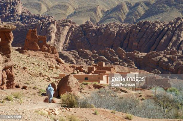 man in djellaba walking along trail before baked mud houses and the bizarre rock formations known as the monkey fingers, dades valley. - country geographic area stock pictures, royalty-free photos & images