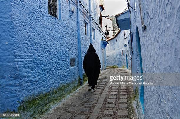 Man in djellaba walking on the blue streets