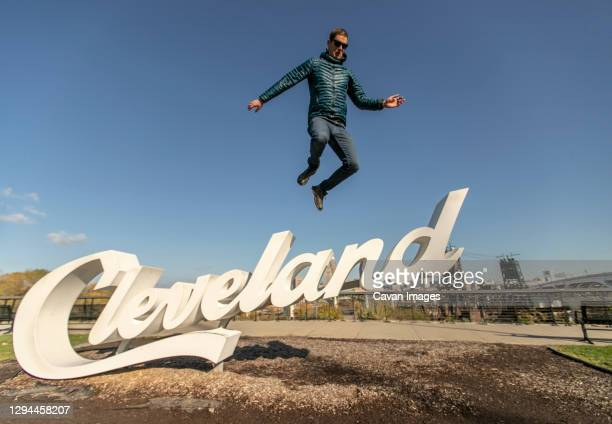man in down jacket leaps jumps of cleveland sign, ohio - cleveland ohio stock pictures, royalty-free photos & images