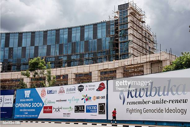 A man in downtown Kigali runs past a billboard for the national 'Kwibuka' campaign aiming at remembering and commemorating the 1994 genocide in...