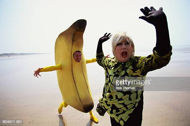 Man in drag being chased along beach by man dressed as banana