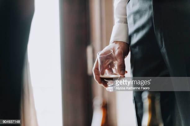 man in dress shirt holds bourbon glass - bourbon whisky foto e immagini stock