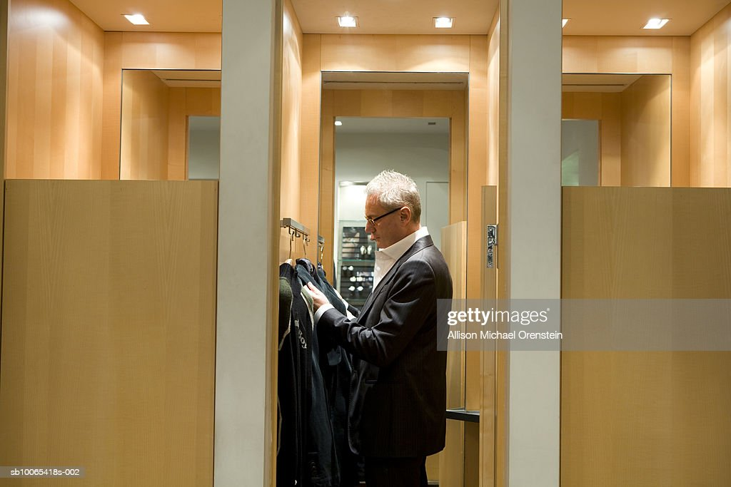 Man in dressing room trying clothes on : Foto stock