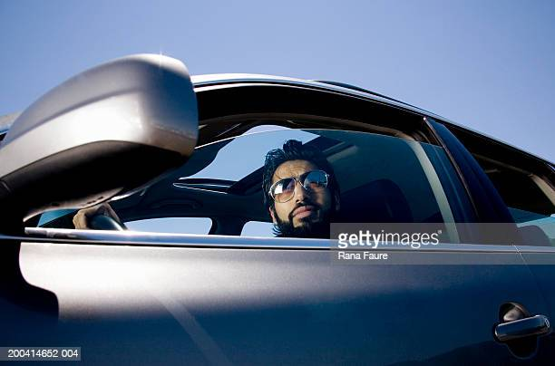 Man in driver's seat looking out window
