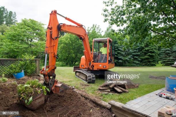 man in earth mover digging soil at construction site - excavator - fotografias e filmes do acervo