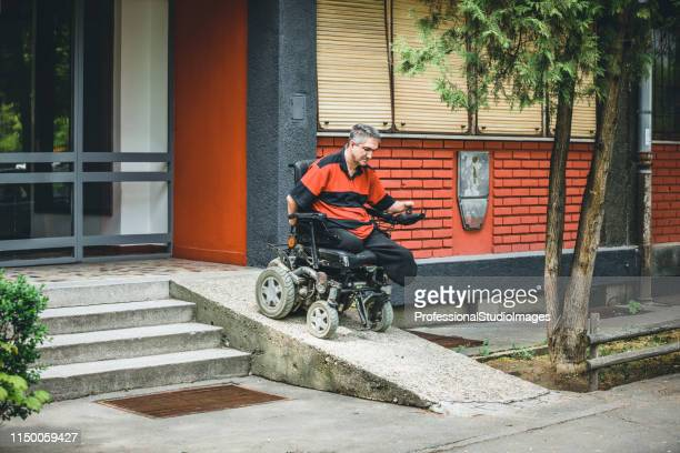 man in electric wheelchair is exiting the building - mobility scooter stock photos and pictures