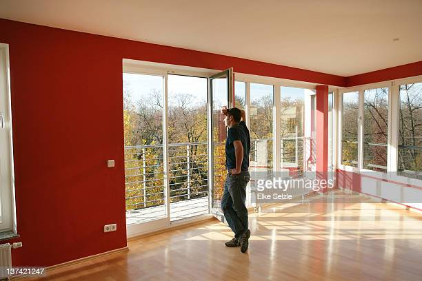 Man in empty apartment leaning on open balcony doo
