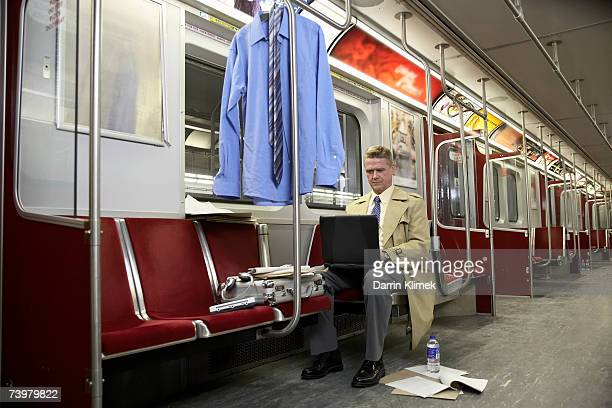 man in empty subway train, using laptop - hot desking photos et images de collection