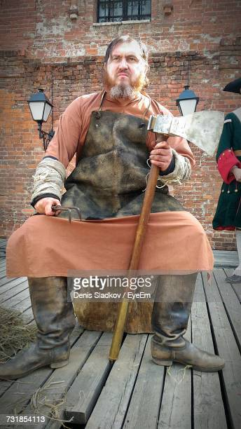 man in executioner costume looking away while sitting against building - medieval shoes stock pictures, royalty-free photos & images