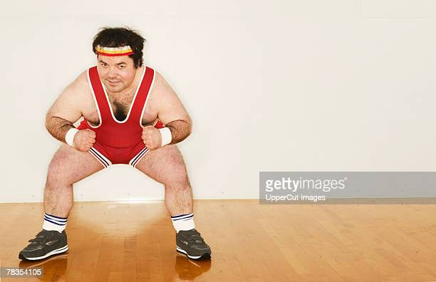 man in exercise gear squatting - hairy man stock pictures, royalty-free photos & images