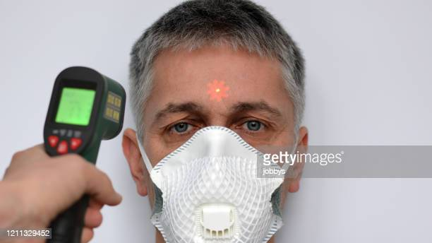 man in face mask having temperature taken with laser thermometer - zakenman stock pictures, royalty-free photos & images