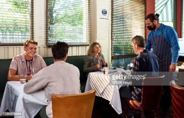 man in face mask serving customers in restaurant - restaurant stock pictures, royalty-free photos & images