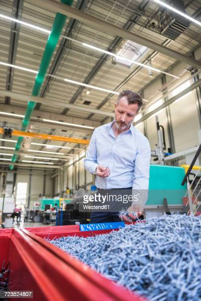 Man in factory examining shred in container