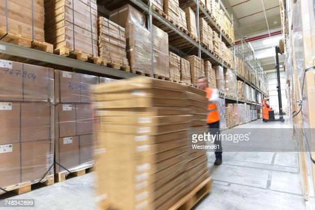 man in factory hall transporting goods - finanzen und wirtschaft stock-fotos und bilder