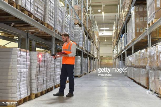 Man in factory hall wearing safety vest holding clipboard scanning goods