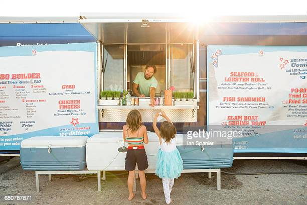 Man in fast food trailer serving two young girls beside trailer