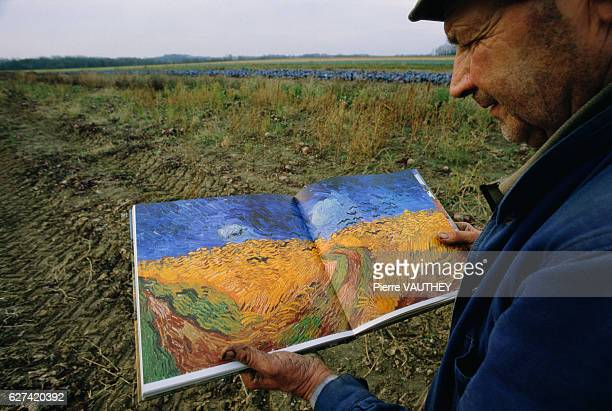 Man in Field Holding Book with Van Gogh's Painting