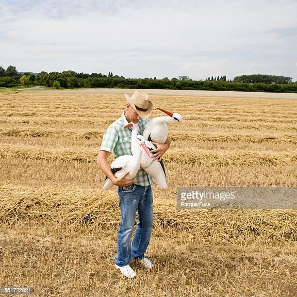 Man in Field Holding Stork Decoys