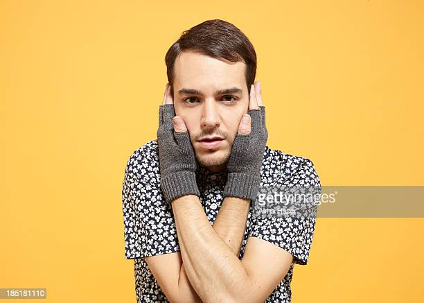 Man in fingerless gloves holding his face