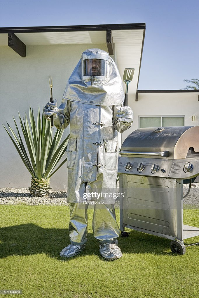 Man in fire-protective suit standing next to grill : Foto de stock
