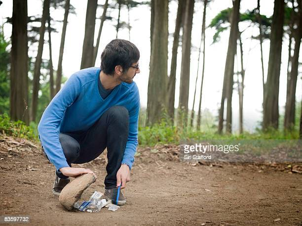 Man in forest sweeping trash under rock