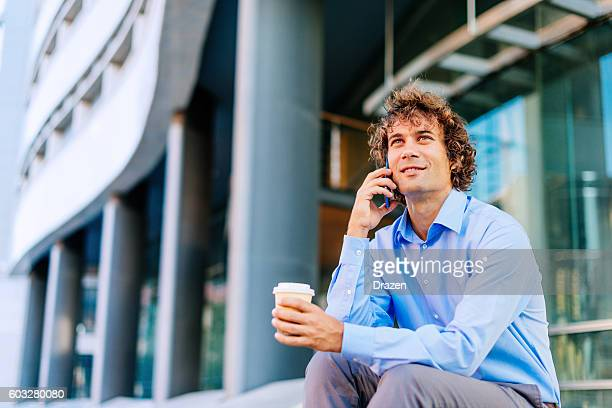 Man in formal clothing sitting and making telephone call