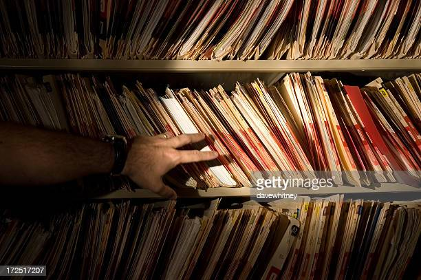 A man in front of a bookshelf of medical records