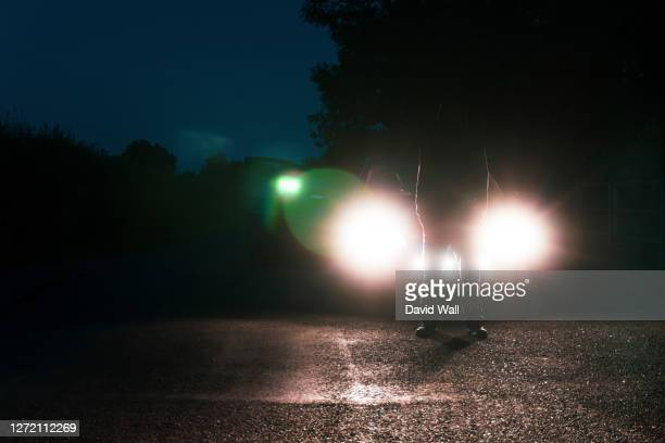 a man in front of a car, standing in the middle of a road, silhouetted against car headlights - criminal stock pictures, royalty-free photos & images